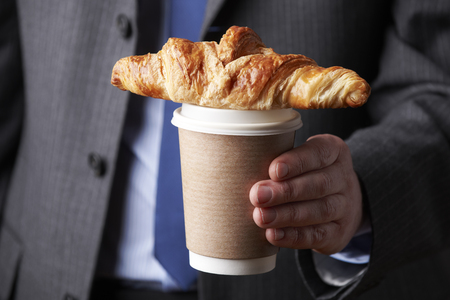 unrecognisable people: Businessman Holding Takeaway Coffee And Croissant Stock Photo