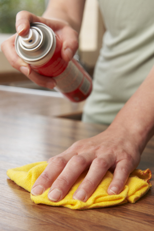 homemaker: Woman Polishing Wooden Surface With Duster Stock Photo