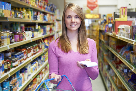 twenties: Portrait Of Woman In Supermarket With Shopping List Stock Photo