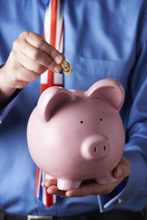 unrecognisable person: Businessman Wearing Union Jack Tie Putting Coin Into Piggy Bank