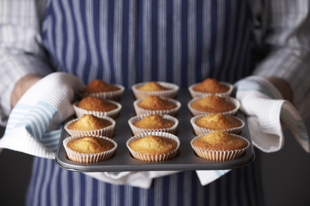 unrecognisable people: Man Holding Tray Of Freshly Baked Homemade Cupcakes