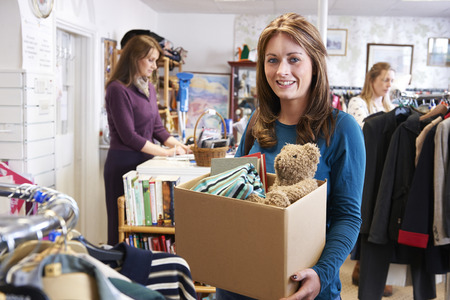 donation: Woman Donating Unwanted Items To Charity Shop