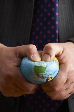 squeezing: Businessman Squeezing Globe Over North America
