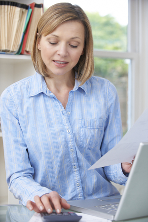 home finances: Woman Working On Domestic Finances In Home Office Stock Photo