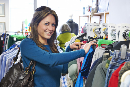 thrift store: Woman Buying Childrens Clothes In Charity Shop