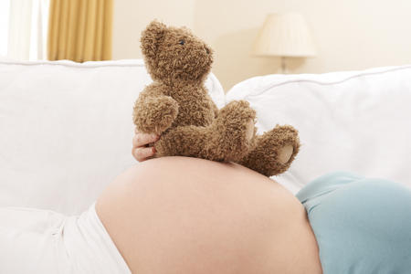 cuddly toy: Pregnant Woman With Cuddly Toy Resting On Bump