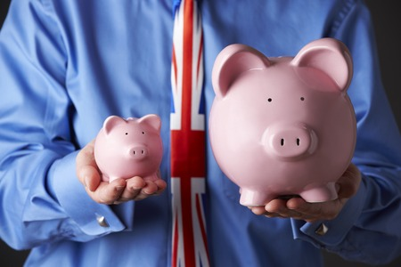 unrecognisable person: British Businessman Holding Large And Small Piggy Bank Stock Photo