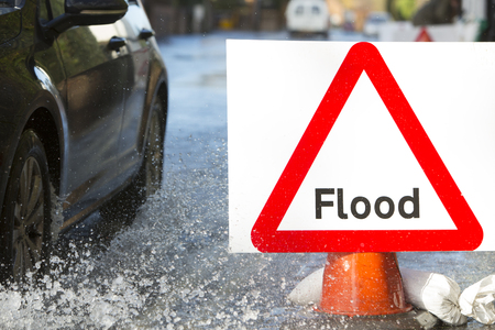 warning signs: Warning Traffic Sign On Flooded Road With Cars