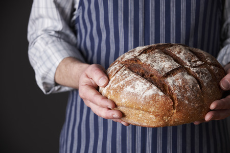 Man Wearing Apron Holding Freshly Baked Loaf Of Bread