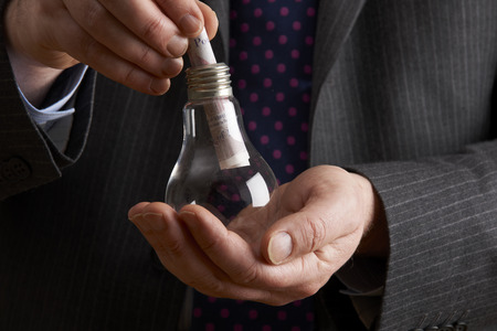 sterling: Businessman Putting Sterling Note Into Light Bulb