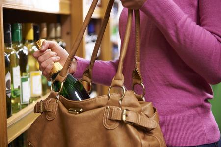 Femme Stealing bouteille de vin Supermarché Banque d'images