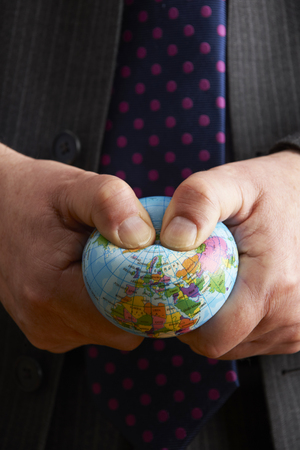 squeezing: Businessman Squeezing Globe Over Europe And Africa Stock Photo