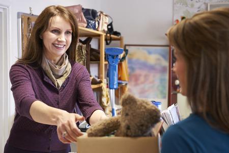 tienda de ropa: Mujer donación de artículos no deseados a la caridad Shop