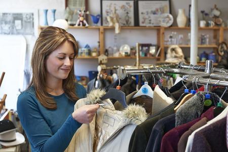 古着屋で女性の買物客は服を見て 写真素材