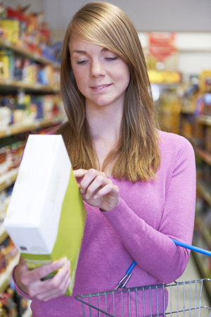 checking ingredients: Woman Checking Labelling On Box In Supermarket Stock Photo