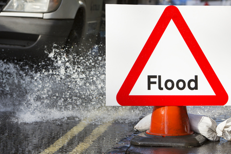 environmental damage: Warning Traffic Sign On Flooded Road With Cars
