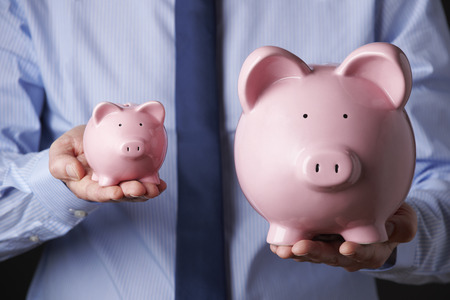 comparisons: Businessman Holding Large And Small Piggy Bank Stock Photo