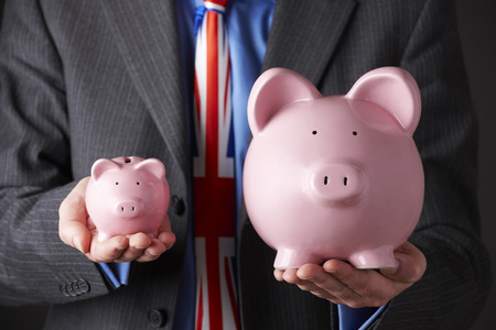 unrecognisable people: British Businessman Holding Large And Small Piggy Bank Stock Photo