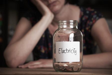 pobreza: Mujer deprimida Mirando a Jar Etiquetado Electricidad