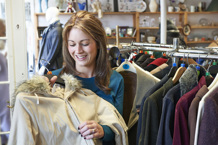 thrift store: Female Shopper In Thrift Store Looking At Clothes