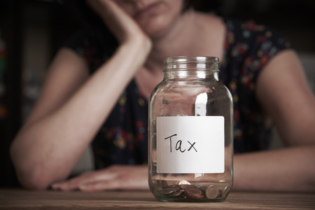 labelled: Depressed Woman Looking At Empty Jar Labelled Tax Stock Photo