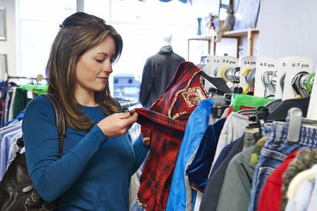 tienda de ropa: Mujer Comprar ropa de los niños en la Caridad Tienda Foto de archivo