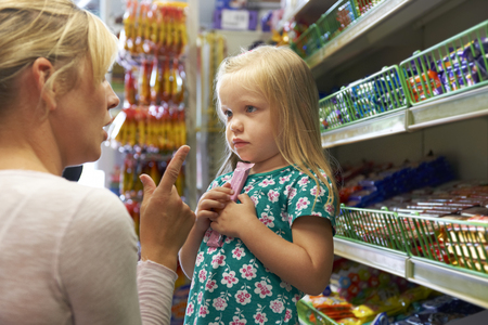 shopping binge: Girl Having Arguement With Mother At Candy Counter In Supermarke