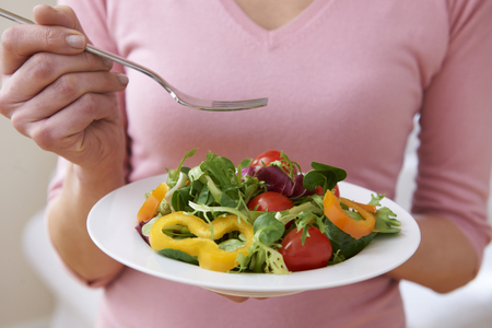 unrecognisable people: Close Up Of Woman Holding Bowl Of Fresh Salad Stock Photo