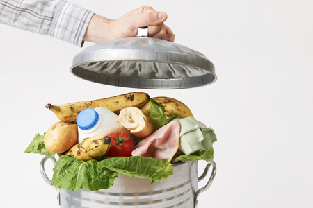 food beverages: Hand Putting Lid On Garbage Can Full Of Waste Food Stock Photo