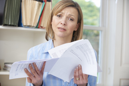 looking at camera: Woman Holding Bills Concerned About Debt