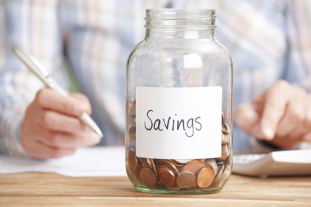 unrecognisable people: Woman Calculating Budget With Savings Jar In Foreground