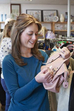 thrift store: Female Shopper In Thrift Store Looking At Handbag