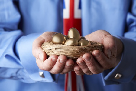 pensions: Businessman Wearing Union Jack Tie Holding Nest Of Golden Eggs