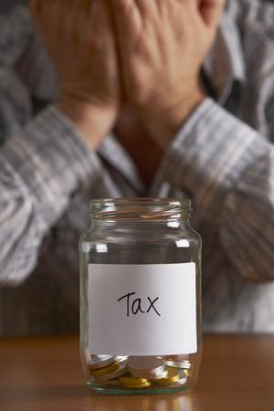 cuenta bancaria: El hombre con la cabeza en las manos mirando a Jar Etiquetado de impuestos Foto de archivo