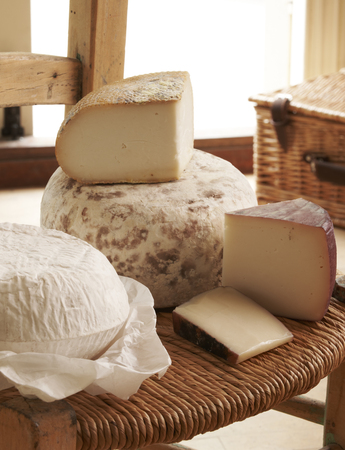 grocers: Display Of Cheese On Rustic Chair Stock Photo