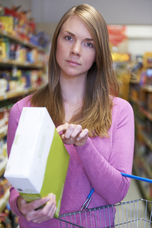 checking ingredients: Worried Woman Checking Contents Of Box In Supermarket