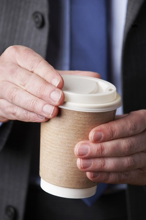 unrecognisable people: Businessman With Cup Of Takeaway Coffee