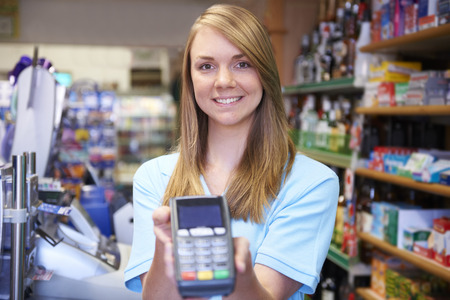 pin entry: Female Sales Assistant Holding Credit Card Machine