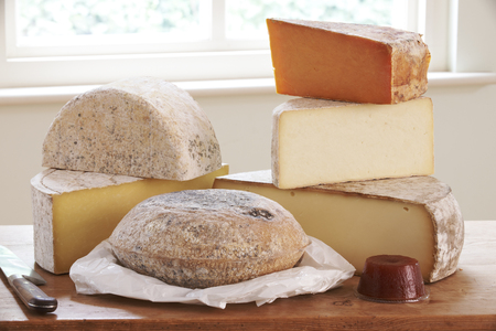 grocers: Selection Of Cheese On Board With Knife Stock Photo