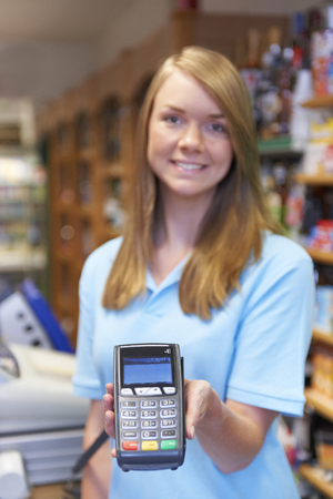 sales assistant: Sales Assistant Holding Credit Card Reader In Supermarket