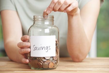 frasco: Mujer que pone la moneda en la jarra de Ahorros etiquetadas Foto de archivo