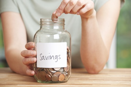 jars: Woman Putting Coin Into Jar Labelled Savings