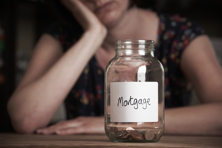 poverty: Depressed Woman Looking At Jar Labelled Mortgage