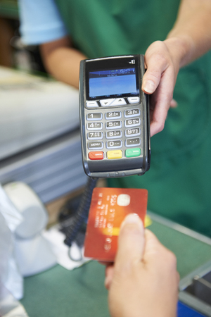 pin entry: Customer Using Credit Card Machine To Pay In Supermarket