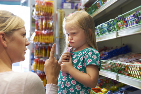 Child Having Arguement With Mother At Candy Counter Stockfoto