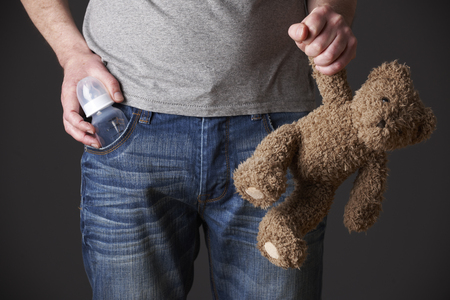unrecognisable person: Father Holding Feeding Bottle And Teddy Bear