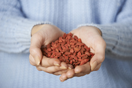 unrecognisable person: Close Up Of Woman Holding Handful Of Goji Berries
