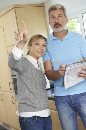 mature woman: Builder Preparing Estimate For Home Improvement
