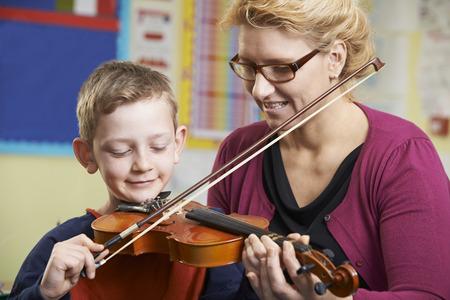 profesores: Estudiantes de ayuda del alumno a tocar el viol�n En la lecci�n de m�sica Foto de archivo