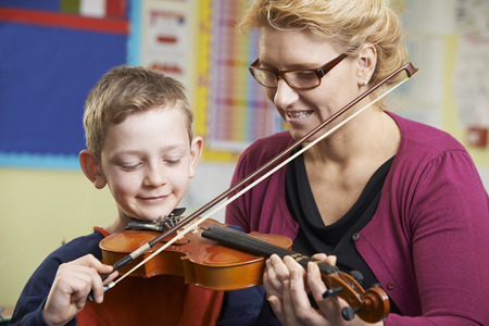 woman violin: Teacher Helping Pupil To Play Violin In Music Lesson
